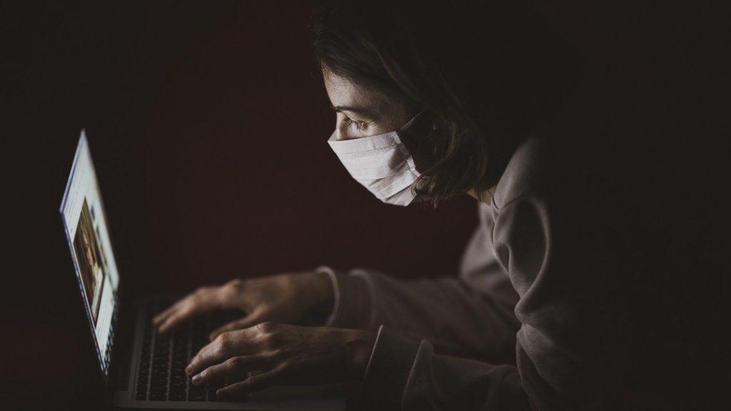 Laptop user wearing mask