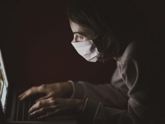 Laptop user wearing mask